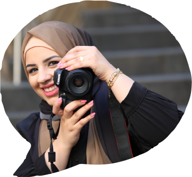 rania abouyounes holding a canon camera and smiling
